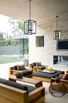 The patio, complete with a fireplace and James Perse teak furniture.   - HarpersBAZAAR.com