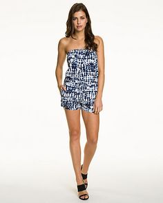 A bold abstract print patterns this flirty sleeveless romper designed with a waist-cinching drawstring waist. #festival