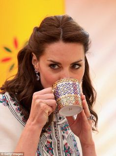 Kate concentrates as she watches the archery contest and drinks from a heavily decorated mug