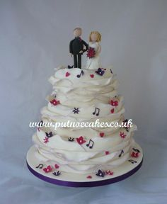 Wrap wedding cake with musical notes, flowers and handmade Bride and Groom topper