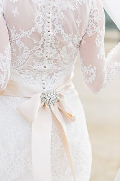 Pretty lace back with an ivory, jeweled bow: http://www.stylemepretty.com/california-weddings/aptos/2015/08/31/rustic-elegant-outdoor-wedding-at-devine-ranch/ | Photography: Bluella - http://bluella.com/