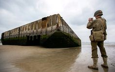 A WWII history enthusiast wearing a replica WWII US military uniform photographs ruins of a landing pontoon on the beach in Arromanches, Normandy, France. Friday June 6 marks the 70th anniversary D-Day