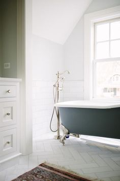 Transitional bathroom features an elegant freestanding black tub accented with silver claw feet and a polished nickel floor mounted tub filler and sprayer positioned beside a single hung window under a slanted ceiling framed by light gray lined with a marble chair rail and white marble subway tile backsplash leading to a floor clad in matching herringbone tiles covered in a pink fringe rug.