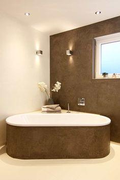 Ovale Badewanne vor der Zimmerecke platziert mit verputzter, grauer Front
