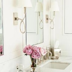 Waterworks Blue Note Sconces flank white framed vanity mirrors hung over a white dual bath vanity fitted with a white and gray honed marble countertop holding sinks with vintage style faucets. Blue Bathroom Interior, White Bathroom Cabinets, Bathroom Countertops, Marble Countertops, Honed Marble, Bathroom Grey, Bathroom Vintage, Waterworks Bathroom, Bathroom Sconces