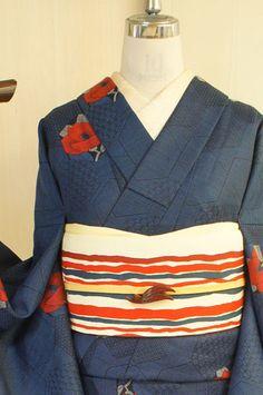 黒と紺青の糸が織りなす濃紺の地に、模様もとりどりな亀甲形の裂を切りばめたような幾何学デザインと、深い赤が美しく映える椿模様が織り出されたウールの単着物です。 Kimono Japan, Yukata Kimono, Blue Kimono, Kimono Outfit, Kimono Fabric, Kimono Fashion, Geisha, Traditional Japanese Kimono, Modern Kimono