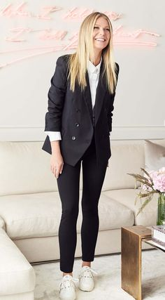 Gwyneth Paltrow in #goopLabel black double-breasted blazer, black leggings, and white button-up shirt with studded sneakers.