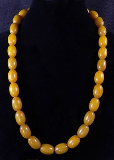 SoVintageous is offering this incredible Art Deco necklace of 30 oval egg yolk amber Bakelite beads in pristine condition.  The beads tested positive for Bakelite using Simichrome and all have a gorge
