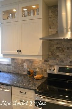 """pearl blue granite countertop and love the rustic tumbled tile backsplash ans the 12"""" glass cabinets above the regular cabinet"""