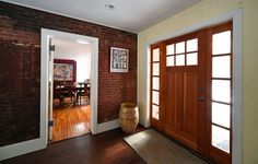 Entryway with wooden front door and exposed brick wall. Plank wood floors, white baseboards and a ceramic pot.