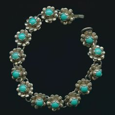A 1940s alpaca silver bracelet of rose links, each with a turquoise glass stone.