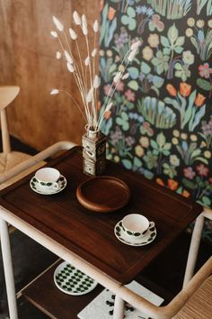 """John says. """"We've used it in our own home""""). The Tea Trolley was designed by Studio Junction for Mjölk, and the 1956 Drawn Dining Chairs are by Hvidt & Mølgaard. The table is set with vintage Bersa coffee cups by Stig Lindberg for Gustavsberg and a vintage Danish teak bowl. The Nils Thorsson Stoneware Vase is from Royal Copenhagen, and the Diamond Pendant Light hanging above was designed by Oji Masanori for Mjolk."""
