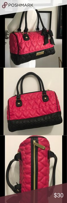 """Betsey JohnsonSatchel Hot Pink Quilted Hearts Betsey JohnsonSatchel Hot Pink Quilted Hearts with black trim, Black bow with rhinestone charm. The """"Betsey"""" gold plaque still has the plastic (pic#5). This bag is in great condition. It has been gently used. There are 2 small stains on the inside, both are no larger than a dime size, they are dark, difficult to see. 1 is above the large zippered pocket on the inside and the other is above the 2 pockets on the other side (pics #7&8) Betsey…"""