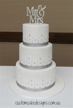 Mr & Mrs Wedding Cake This elegant and simple design was chosen by the bride to match their silver and white wedding theme. This cake...