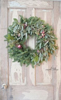 DIY way to customize a fresh evergreen Christmas wreath with flowers and eucalyptus
