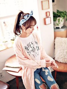 Banda en el cabello y jeans rotos con un gran suéter rosa