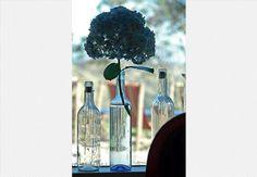 Uma das garrafas com flores recebeu um rótulo especial: o número da mesa. Ideia simples e original