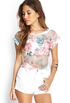 This knit crop top features a romantic rose print and jersey mesh paneling. Finished with a round neckline and short sleeves, pair with distressed white denim for a fresh Spring look.
