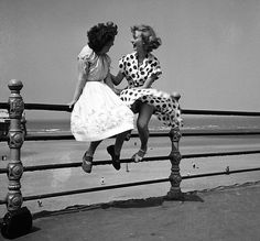 """Bert Hardy - """"Maids in Waiting"""" Two young women chat as they sit on the  seafront promenade railings in Blackpool, Lancashire, UK, Summer 1951."""