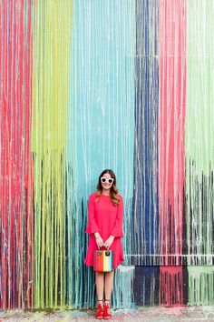 Jennifer Lake Style Charade in a Kate Spade pink ruffle dress, Sophie Hulme rainbow stripe Albion tote, Loeffler Randall Luz sandals at Biscuit Wall Houston Graffiti Wall, Wall Murals, Wall Hangings, Pink Ruffle Dress, Drip Painting, Bold And The Beautiful, Happy Colors, Look Fashion, Street Graffiti