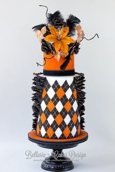 Black and orange Argyle inspired double barrel cake with a touch of gold - Argyle inspired double barrel ruffles cake. I like the combination of black, orange and a touch of gold. At the top I have made an orange sugar Lily and black roses. I hope you like it.  Bellaria Cakes Design www.bellariacakesdesign.nl or  www.facebook.com/bellariacakesdesign