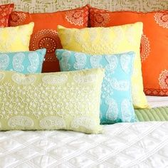 An array of #orange and #blue pillows and the scent of #hibiscus bring a #Hawaiian sunset to your bedroom.