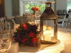 Sobre base plateada, farol y ramo de flores.
