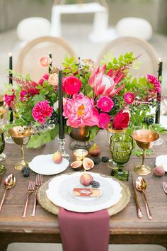 Gold goblets, mossy-green pressed glassware, and a scattering of fruit gave the tablescape an old-world vibe. The brightness of the centerpiece—made up of king proteas, peonies, roses, dahlias, berries, astilbes, ranunculi, and foliage—was balanced by black taper candles, which lent a tinge of moodiness. | Photo by Allison Maginn