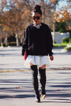 Oversized sweater, pleaded white skirt, with black thigh high boots, and a beautiful silver statement piece necklace .
