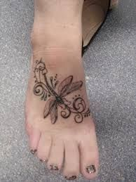 Lovely simple dragonfly tattoo on foot - mostly black so would not fade too much either!