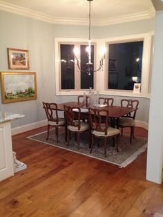 The dining room comes together with the help of this rug and stacked paintings.