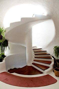 joli escalier tournant blanc avec bois foncé et plantes vertes d'intérieur