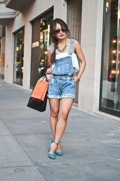 shopping bags held by a brunette woman, with braided hair, wearing short denim overalls, and turquoise high heels, 90s aesthetic, white off-the-shoulder blouse