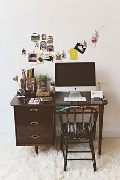 A small office desk for a bedroom or small apartment. We just love the dark wood table and personalized Polaroid art decor.