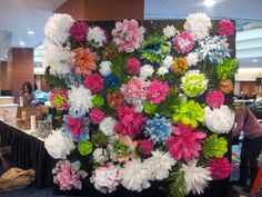 multi-color tissue paper flowers hot glued to plywood stands