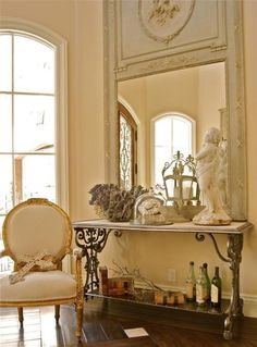 A few of my favorite things: antiques,  beautiful furniture, an eclectic style European mix with primary French inspiration, high ceilings and a lovely framed grand scale mirror amongst a calming neutral palette.