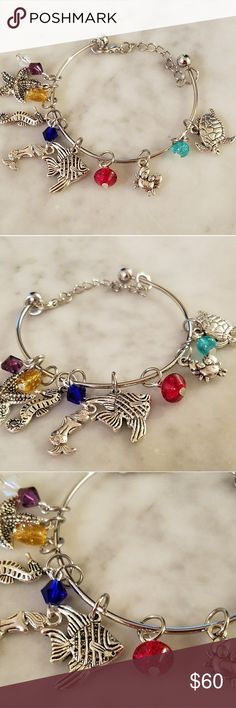 Treasures Below Collection Charm Bracelet 10 charms!!! Tibetan Silver charms and a mix of swavorski crystals and glass bead handmade charms. On a silver cuff style bracelet. The ball ends unscrew. I have added a chain and clasp to this cuff bracelet to help the bracelet stay on your wrist with put worrying that may fly off, since it has some weight to it.   I do not have much wiggle room on the price but feel free to make an offer.  Magen's Fairytale Creations original handmade by me…