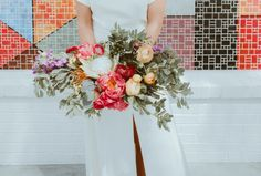 This vibrant and loose bouquet is all kinds of wonderful. The muted tones of the leaves perfectly complement the saturated florals.