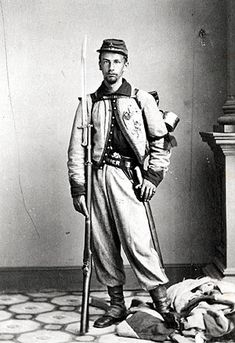 Col. Elmer E. Ellsworths avenger, Private Francis E. Brownell, is seen in this photograph by Mathew Brady dressed in his Zouave uniform and wearing a mourning band tied around his left arm. He is standing on the secession flag taken from the Marshall House. He is holding the rifle with the sword bayonet with which he used to kill the Alexandria secessionist, James W. Jackson.