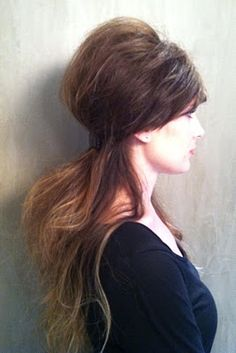 Step 1: Apply Dry Shampoo on roots and ends to add volume and gently cleanse.    Step 2: In front, create an extreme side part to sweep across the forehead. Step 3: Add height to the top by teasing the crown. Step 4: Create a partial up-do. Pull back the top section of your hair to the nape of the neck, and secure with hair pins. Step 5: Cover pins with a clip or barrette.