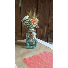 Simple table setting. Carnations and babies breathe in mason jar, with decorated horse shoe propped. Burlap and coral table runner.