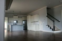 3 Bed, 2.5 Bath   Clifton Development Group, LLC. open floor plan, white kitchen, gray walls, black stair railing, modern bungalow