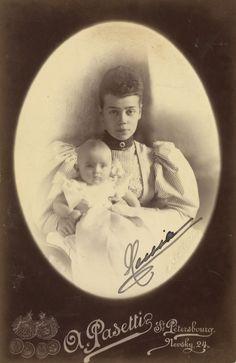 """Grã-duquesa Xenia Alexandrovna e Princesa Irina Alexandrovna. Grã-duquesa Xenia está vestindo uma blusa com mangas compridas em um padrão listrado e está segurando a bebê Princesa Irina em seu joelho. A fotografia é assinada """"Xenia '. Em 1895."""