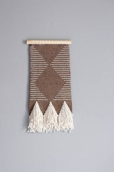 This weaving was handwoven on a frame loom and features a negative space geometric design with clean lines. The main yarn used for this piece is 50% organic wool and 50% organic cotton and is dyed with Global Organic Textile Standard low-impact dye. Along the bottom you will fine a