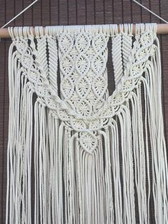 A beautifully hand made 100% cotton macrame wall hanging. Intricate craft work and truly one of my best so far. Woven onto a Cherry wood hanger. Measures 50 cm x 90 cm without the pole and weighs approximately 1.6 kg.