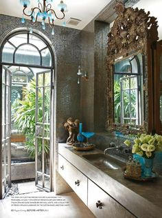 A GORGEOUS brown bathroom with an early 18th century French mirror and glass mosaic tiles accented with a turquoise blue opaline glass by flora