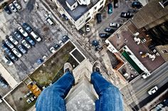 Photographer Dennis Maitland takes pictures of Detroit from above dangling his feet below.