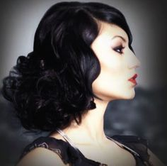 Dramatic updo. I love how bold her dark hair is against her skin.  Very James Bond!