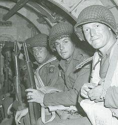 """Ces hommes de la 82nd Airborne sont des """"Gliders"""" (infanterie aéroplanée). ils ont pris place dans un planeur malgrè le sourire pour la photo, la tension est perceptible. La forme arrondie du fuselage indique qu'il s'agit d'un """"Horsa"""" britannique. Les hommes portent tous le gilet de sauvetage en prévision du vol au-dessus de la Manche. England, june 5 1944 Us Marshals, Ww2 History, Band Of Brothers, Paratrooper, D Day, Us Army, American, World War, About Uk"""