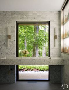 A MODERN CONNECTICUT HOUSE PAYS HOMAGE TO MIDCENTURY STYLE Specht Harpman Architects and the design team Carrier and Co. remake a nondescript dwelling in New Canaan as a polished take on postwar architecture  Nickel sconces by Casella Lighting frame the window in the downstairs bath; the sink fittings are by Hansgrohe, and the wall and floor tiles are from Stone Source.
